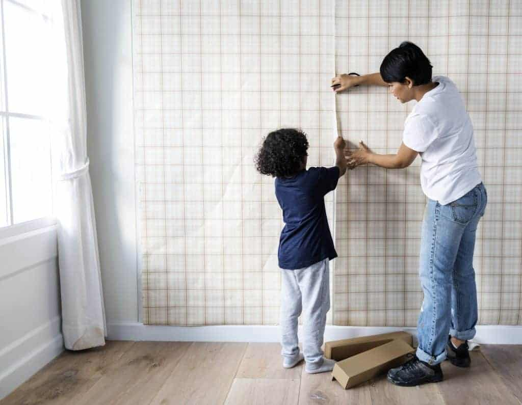 Kid helping mom install wallpaper